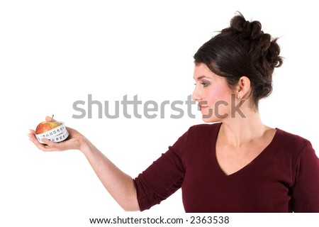 Pretty brunette holding an apple out that is surrounded by measuring tape - stock photo
