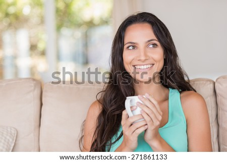 Pretty brunette holding her mug at home in the living room - stock photo