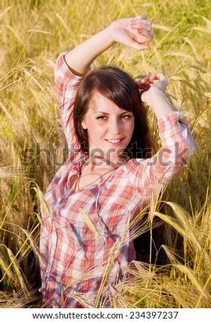 Pretty brunette in a field of rye - stock photo