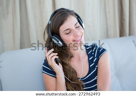Pretty brunette listening music on couch in the living room - stock photo