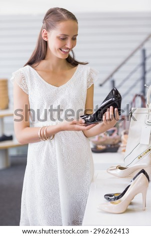 Pretty brunette looking at a heel shoe in shoe store - stock photo