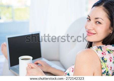 Pretty brunette looking at camera and using laptop on couch at home - stock photo