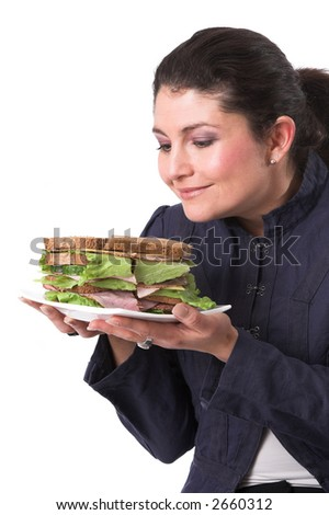 Pretty brunette looking to her sandwich, clearly looking forward to eating it - stock photo