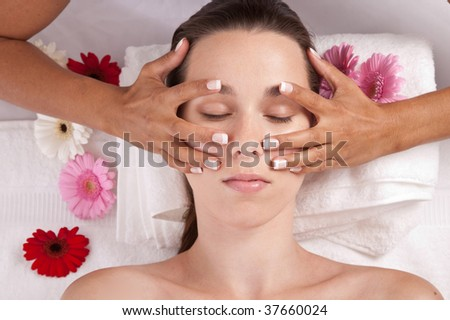 Pretty brunette lying in a spa salon and getting a facial massage - stock photo