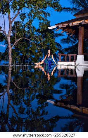 Pretty brunette model in beautiful mottled beach dress posing at the pool with reflection of the evening sky - stock photo
