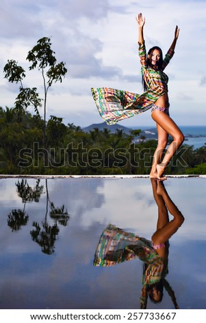 Pretty brunette model in bikini and beach dress posing at the pool with reflection of the evening sky in the water  - stock photo