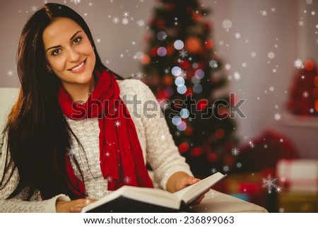 Pretty brunette reading on couch at christmas against snow falling - stock photo