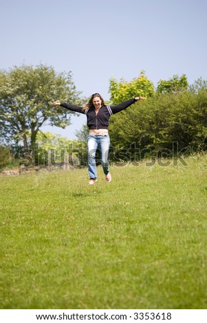 Pretty brunette running down the hill with a happy grin on her face (some movement due to running) - stock photo