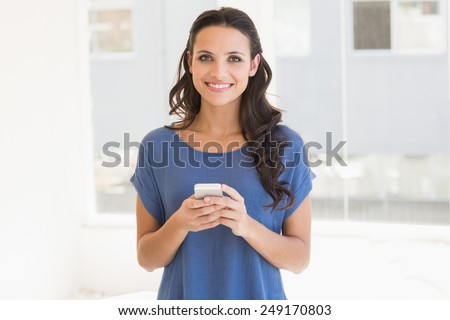 Pretty brunette sending a text at home beside window - stock photo