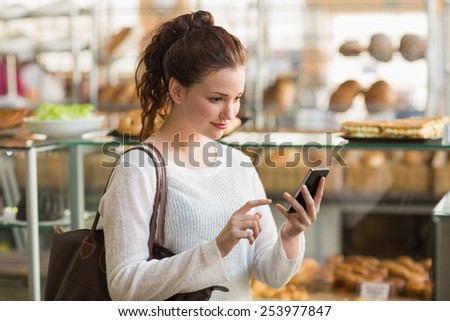 Pretty brunette sending a text at the bakery - stock photo