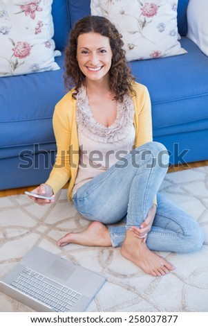 Pretty brunette sitting on the floor and using her smartphone in the living room - stock photo