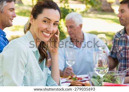 Pretty brunette smiling at camera during a picnic on a sunny day - stock photo