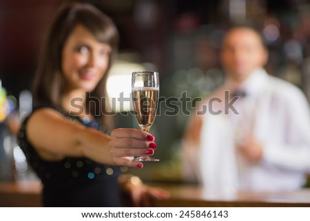 Pretty brunette smiling at camera with champagne in a bar - stock photo