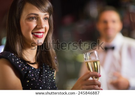 Pretty brunette smiling with champagne in a bar - stock photo