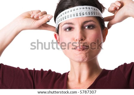 Pretty brunette sticking out her tongue and holding the measuring tape around her head in a protest against all diets - stock photo