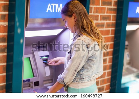 Pretty brunette student withdrawing cash at an ATM - stock photo