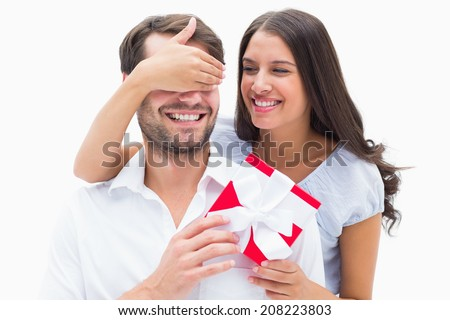 Pretty brunette surprising boyfriend with a gift on white background - stock photo
