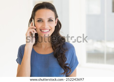 Pretty brunette talking on phone at home beside window - stock photo