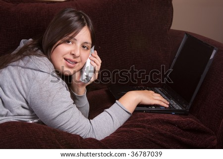 Pretty brunette teenage Hispanic girl laying on the sofa and typing on laptop and talking on a cordless phone - stock photo