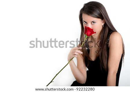 Pretty Brunette wearing a Heart Necklace smelling a Red Rose - stock photo