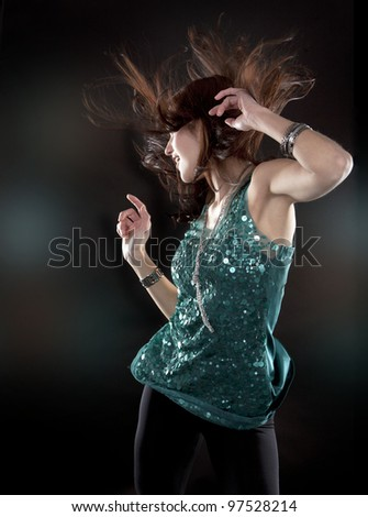 pretty brunette wearing green outfit on black background - stock photo