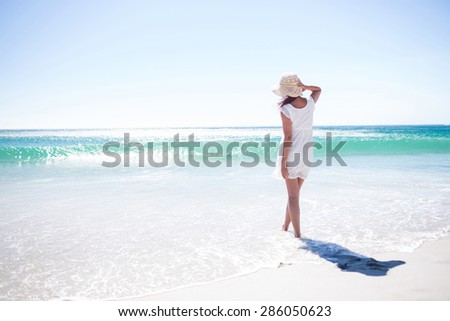 Pretty brunette wearing straw hat and walking in the water at the beach - stock photo