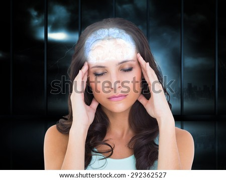 Pretty brunette with a headache against room with large window looking on city - stock photo