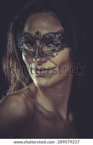Pretty brunette woman in black mask metal frills - stock photo