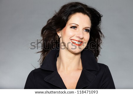 Pretty brunette woman in winter fashion studio shot against grey background. - stock photo