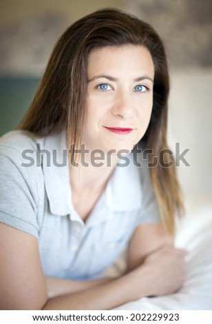 Pretty brunette woman lying on a bed - stock photo