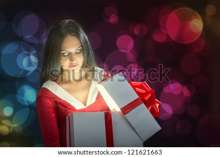 Pretty brunette woman opening the magic Christmas present box - stock photo