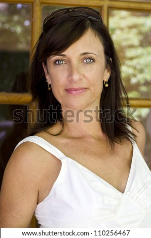 Pretty brunette woman stepping outside on a Spring morning - stock photo