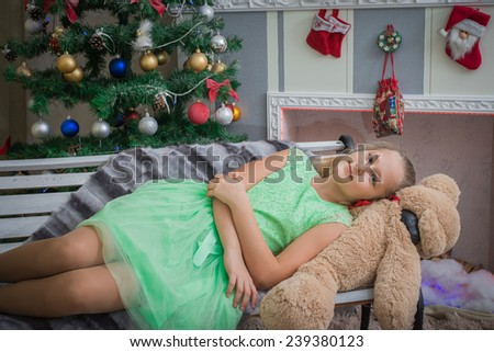 Pretty brunette woman wearing a warm knitted sweater, lying on a fur cover on the floor near decorated Christmas tree in a living room, reading a book. Many presents and pillows nearby. - stock photo