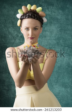 Pretty, brunette woman with funny hairstyle with easter eggs. She wears yellow bra and dress. She is holding some feathers. - stock photo