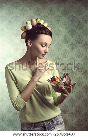 Pretty, brunette woman with funny hairstyle with eggs, and looking on little easter basket with decorations. - stock photo
