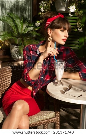 Pretty brunette woman with long legs in red skirt, checked shirt band, black patent leather high heels resting in a wickered chair in a street cafe drinking cold milk shake cocktail. On hot summer day - stock photo