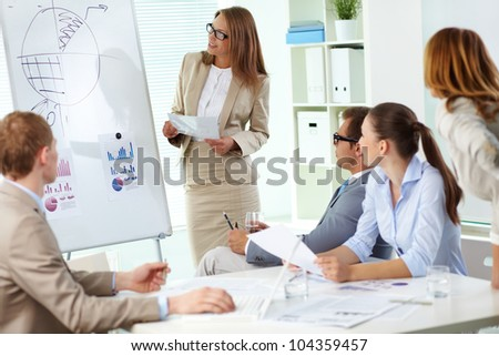 Pretty business lady reporting on business results of the financial period - stock photo