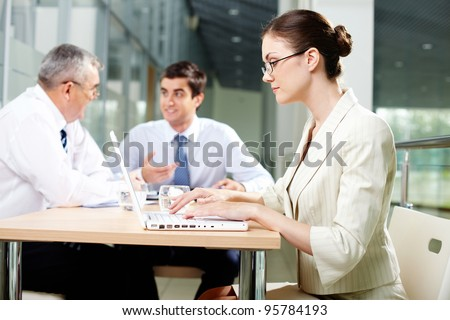 Pretty business lady working on a laptop while her male colleagues discussing business project - stock photo