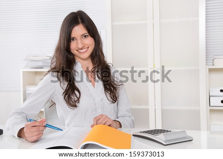 Pretty business woman smiling at desk in her office  - stock photo