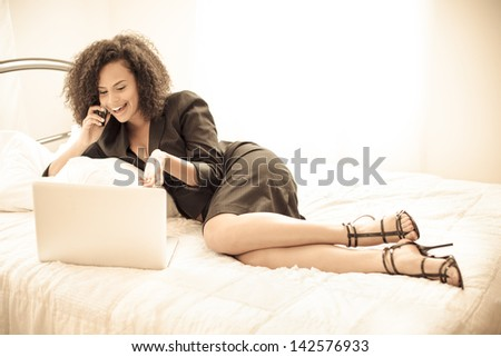 Pretty business woman smiling on her cell phone and computer - stock photo