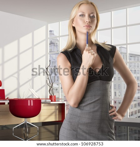 pretty business woman with elegant dress and pen, she is in front of the camera, takes the pen with right hand near the chin and looks in to the lens with serious expression - stock photo