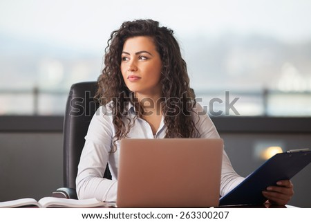 pretty business woman with notebook in the office - stock photo