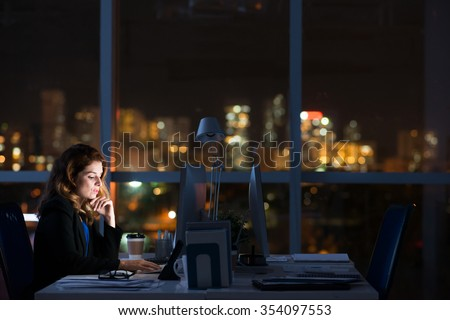 Pretty business woman working alone in dark office - stock photo