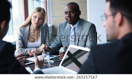 Pretty businesswoman and confident man listening to colleague at meeting - stock photo