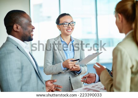 Pretty businesswoman discussing plans or ideas with her colleagues in office - stock photo