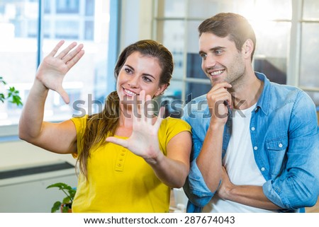Pretty businesswoman doing frame with her hands and showing to her partner in the office - stock photo