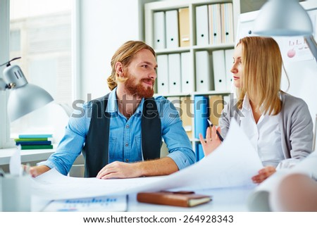 Pretty businesswoman explaining to colleague her ideas about new project - stock photo