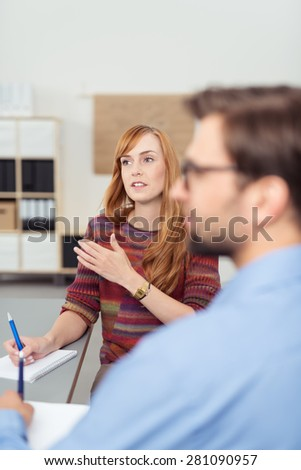 Pretty businesswoman in a meeting discussing a project on her computer monitor with a male colleague gesturing as she gives an explanation - stock photo