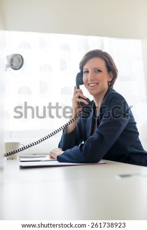 Pretty businesswoman in blue suit smiling as she  calling someone through telephone at her worktable conceptual of a call center or business communication. - stock photo