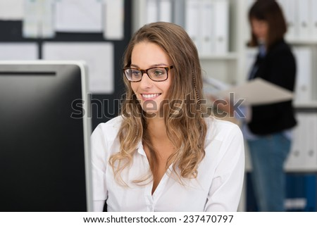 Pretty businesswoman in glasses working at her computer in the office reading her monitor with a smile - stock photo